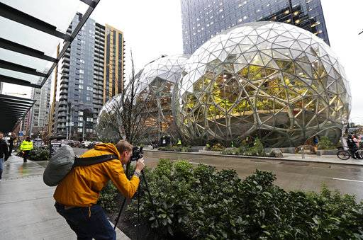 Alex Crook, a photographer with Seattle Magazine, photographs the Amazon Spheres in downtown Seattle on the day of their grand opening, Monday, Jan. 29, 2018, in Seattle.