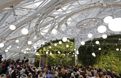 Guests listen as Jeff Bezos, the CEO and founder of Amazon.com, speaks during the grand opening of the Amazon Spheres, Monday, Jan. 29, 2018, in Seattle.