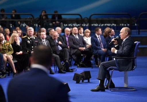 "Russian President Vladimir Putin, right, speaks to his supporters during a meeting for his campaign in Moscow, Russia, Tuesday, Jan. 30, 2018. Putin said on Tuesday the Trump administration made a ""hostile step"" when it published a list of Russian businessmen and politicians as part of a sanctions law against Moscow. (Alexei Nikolsky, Sputnik, Kremlin Pool Photo via AP)"
