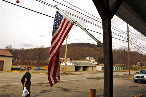 With Ed's Car Wash in the background at center, a person looks on in Saltlick Township, Pa., Monday, Jan. 29, 2018. Pennsylvania State Police said a man opened fire at the car wash around 3 a.m. Sunday morning, killing several.
