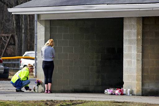 Flowers and a candle are placed at Ed's Car Wash in Saltlick Township, Pa., on Monday, Jan. 29, 2018. Pennsylvania State Police said a man opened fire at the car wash around 3 a.m. Sunday morning, killing several.