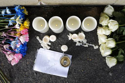 Flowers, candles and a note are left at a memorial near Ed's Car Wash after a deadly shooting Monday, Jan. 29, 2018, in Saltlick Township, Pa. State police said Timothy Smith opened fire early Sunday morning at the car wash, killing several.