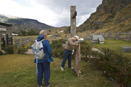 Friends of the late American conservationist Doug Tompkins visit his tomb before the start of a signing ceremony in Patagonia Park, Chile, Monday, Jan. 29, 2018. Chile's president signed decrees creating vast new national parks using lands donated by the Tompkins Conservation, in what is believed to be the largest private donation of land ever from a private entity to a country.