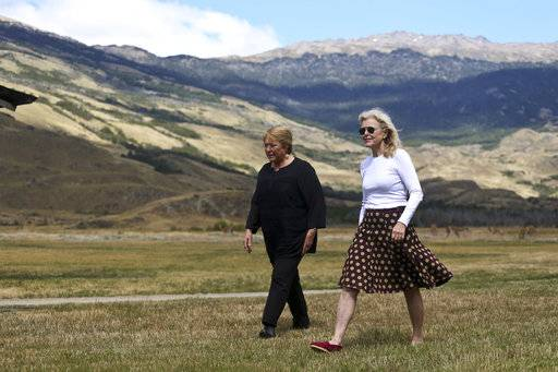 Chilean President Michelle Bachelet, left center, and Kristine McDivitt Tompkins, widow of the late American conservationist Doug Tompkins, walk prior to the start of a ceremony in Patagonia Park, Chile, Monday, Jan. 29, 2018. Bachelet signed decrees creating vast new national parks using lands donated by the Tompkins Conservation, in what is believed to be the largest private donation of land ever from a private entity to a country.