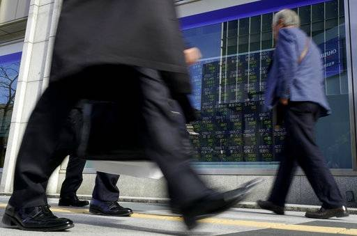 People walk past an electronic stock indicator of a securities firm in Tokyo, Tuesday, Jan. 30, 2018. Asian shares were lower Tuesday following Wall Street's biggest loss in more than four months.