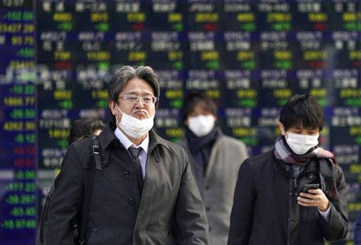 People walk in front of an electronic stock indicator of a securities firm in Tokyo, Tuesday, Jan. 30, 2018. Asian shares were lower Tuesday following Wall Street's biggest loss in more than four months.