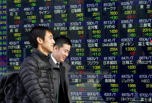 Men walk past an electronic stock indicator of a securities firm in Tokyo, Tuesday, Jan. 30, 2018. Asian shares were lower Tuesday following Wall Street's biggest loss in more than four months.