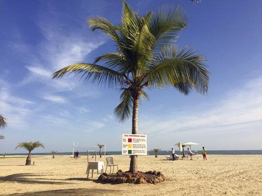 FILE - In this Jan. 17, 2017, file photo, tourists lay on the beach in Gambia's capital Banjul. A shore excursion in Gambia on a monthlong cruise of Africa offers scenery, adventure and cultural immersion.