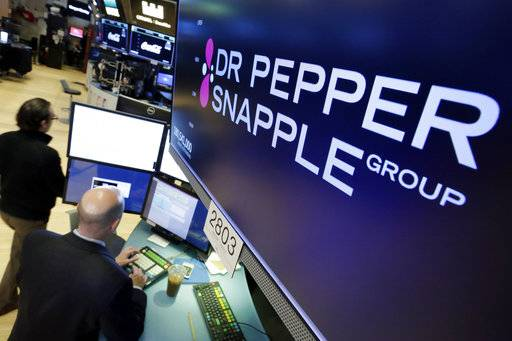 The Dr. Pepper Snapple Group logo appears above a trading post on the floor of the New York Stock Exchange, Monday, Jan. 29, 2018. Keurig is buying Dr. Pepper Snapple Group Inc., creating a beverage giant with about $11 billion in annual sales.