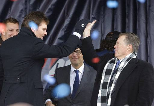 New England Patriots quarterback Tom Brady, front left, exchanges a high five with head coach Bill Belichick, right, during an NFL football Super Bowl send-off rally, Monday, Jan. 29, 2018, in Foxborough, Mass. The Patriots are to play the Philadelphia Eagles in Super Bowl 52, Sunday, Feb. 4, in Minneapolis. Patriots tight end Rob Gronkowski, left, and Jonathan Kraft, president of the Kraft Group, behind center, look on.