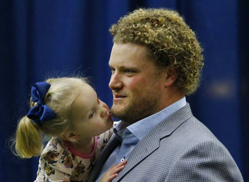 Buffalo Bills center Eric Wood is kissed by daughter Grace following a press conference announcing he has been diagnosed with a career ending neck injury, Monday, Jan. 29, 2018, in Orchard Park, N.Y.