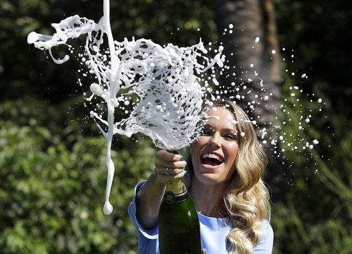Denmark's Caroline Wozniacki sprays champagne during a photo shoot in the Royal Botanical Gardens in Melbourne, Australia, Sunday, Jan. 28, 2018. Wozniacki defeated Romania's Simona Halep in Saturday's final to win the Australian Open women's singles final.