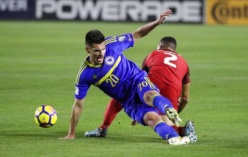 Bosnia and Herzegovina midfielder Goran Zakaric, left, and United States defender Justin Morrow tumble as they fight for the ball during the first half of an international friendly soccer match on Sunday, Jan. 28, 2018, in Carson, Calif.
