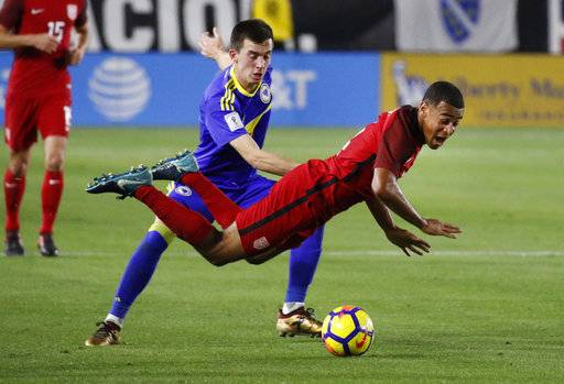 United States midfielder Tyler Adams, front, falls as Bosnia and Herzegovina midfielder Marijan Cavar defends during the second half of an international friendly soccer match on Sunday, Jan. 28, 2018, in Carson, Calif. The game ended in a 0-0 draw.