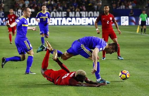 United States midfielder Gyasi Zardes, bottom, falls to the ground after he was pushed by Bosnia and Herzegovina defender Daniel Graovac during the first half of an international friendly soccer match on Sunday, Jan. 28, 2018, in Carson, Calif.