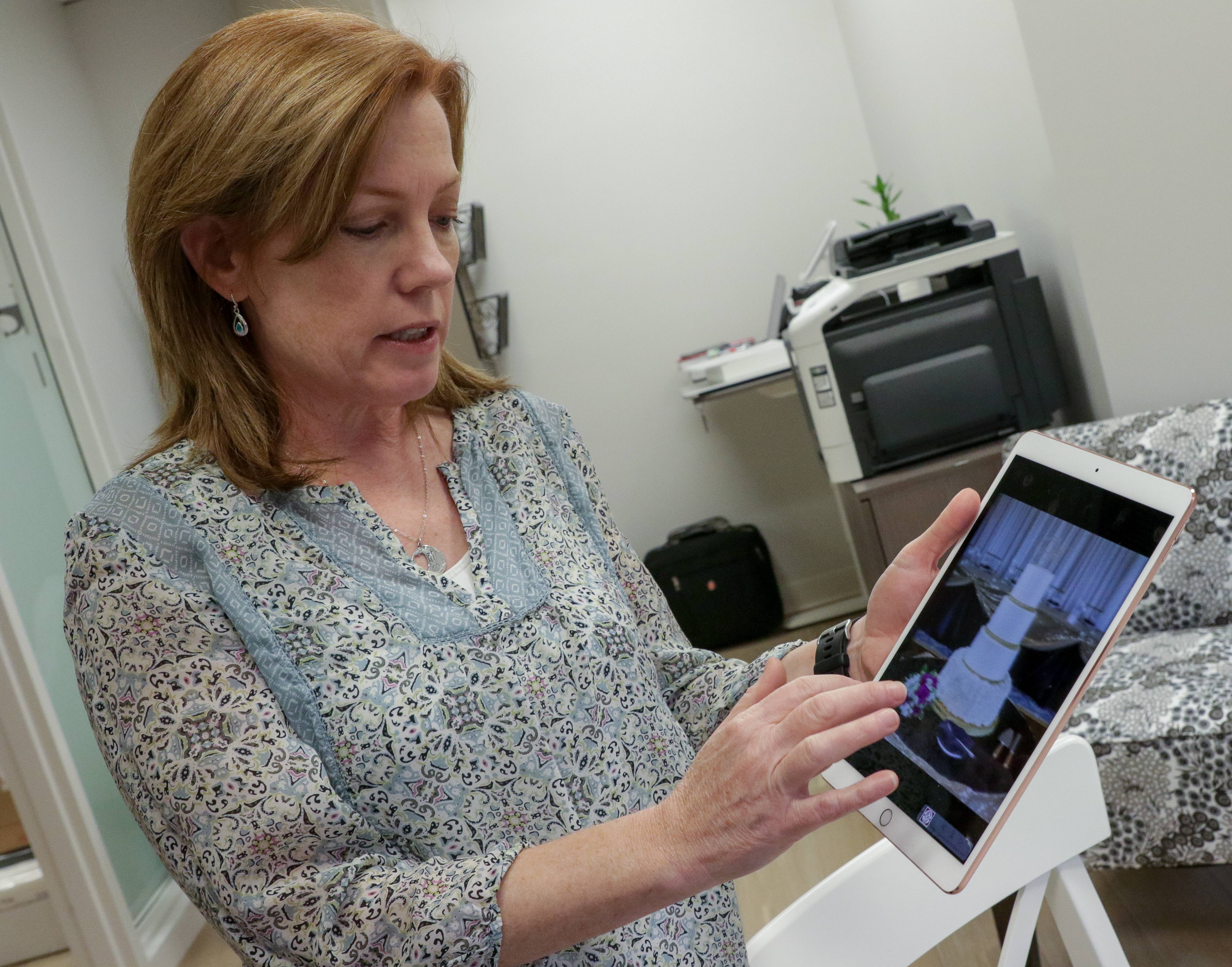 Beth Fahey of Creative Cakes Design Studio in Naperville uses an iPad and a TV screen to display social media photos of cakes her customers provide as inspiration and then to design her own creations. The downtown Naperville design studio opened last week.