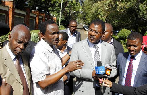 "Former Kenyan vice president Kalonzo Musyoka, second left, stands outside his home to address journalists, in Nairobi, Kenya, Wednesday, Jan. 31, 2018. Musyoka said Wednesday gunshots were fired at his home and a grenade detonated in what he described as ""an assassination attempt.�"