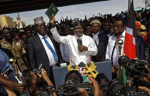 "FILE - In this Tuesday, Jan. 30, 2018 file photo, opposition leader Raila Odinga, center, accompanied by lawyers Miguna Miguna, center-left, Tom ""T.J."" Kajwang, center-right, and politician James Orengo, right, holds a bible aloft after swearing an oath during a mock ""swearing-in"" ceremony at Uhuru Park in downtown Nairobi, Kenya. The lawyer for Kajwang, who stood by Odinga in judicial dress during the ceremony, said Wednesday that he had been arrested."