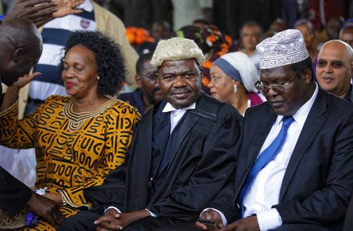 "Lawyers Tom ""T.J."" Kajwang, center, and Miguna Miguna, center-right, attend a mock ""swearing-in"" ceremony for opposition leader Raila Odinga at Uhuru Park in downtown Nairobi, Kenya Tuesday, Jan. 30, 2018. The lawyer for Kajwang, who stood by Odinga in judicial dress during the ceremony, said Wednesday that he had been arrested."