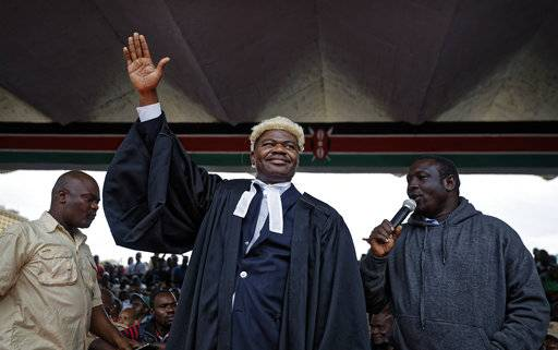 "Opposition legislator and lawyer Tom ""T.J."" Kajwang, center, gestures to the crowd as he attends a mock ""swearing-in"" ceremony for opposition leader Raila Odinga at Uhuru Park in downtown Nairobi, Kenya Tuesday, Jan. 30, 2018. The lawyer for Kajwang, who stood by Odinga in judicial dress during the ceremony, said Wednesday that he had been arrested."