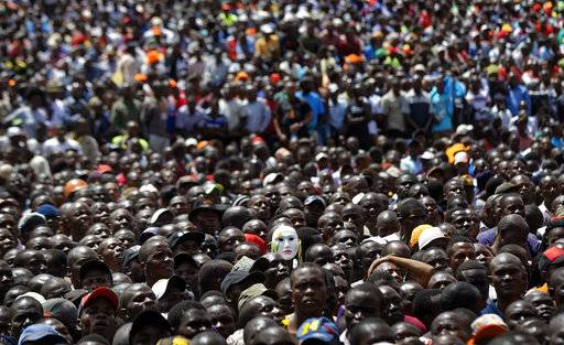 "Supporters of opposition leader Raila Odinga, one wearing a mask, attend a mock ""swearing-in"" ceremony at Uhuru Park in downtown Nairobi, Kenya Tuesday, Jan. 30, 2018. Odinga was sworn-in as ""the people's president"" during a mock ""inauguration"", in protest of President Uhuru Kenyatta's new term following the divisive 2017 election, and despite the government's warning that the event would be considered treason."