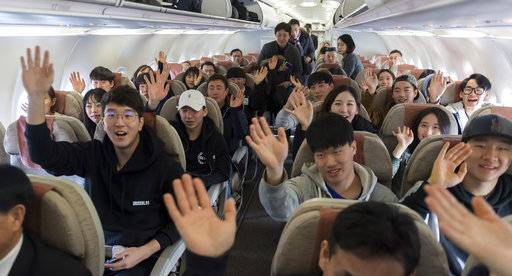 South Korean skiers on the chartered flight wave to the media before taking off to North Korea at Yangyang International Airport in Yangyang, South Korea, Wednesday, Jan. 31, 2018. Several South Korean skiers headed to North Korea on Wednesday to train with its athletes in a conciliatory gesture the countries planned to mark the Winter Olympics in the South. (Korea Pool/Yonhap via AP)