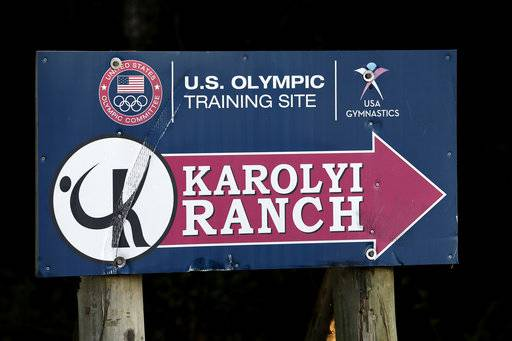 In this Sept, 12, 2015 photo, a sign points down the road to the Karolyi Ranch near New Waverly, Texas. Texas Gov. Greg Abbott on Tuesday, Jan. 30, 2018, has ordered a criminal investigation into claims that former doctor Larry Nassar abused some of his victims at the Texas ranch that was the training ground for U.S. women's gymnastics .