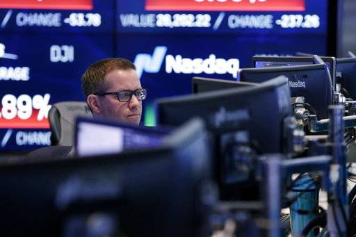 A Nasdaq employee works at the Nasdaq MarketSite, in New York, Tuesday, Jan. 30, 2018. Health care stocks are leading U.S. indexes broadly lower in early trading following news of a big new venture in the health care business.