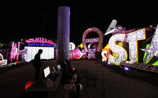 In this Jan. 24, 2018, photo, digital artist and designer Craig Winslow, left, works on an exhibit at the Neon Museum in Las Vegas. Starting this week, visitors will be able to see many of the city's classic neon signs just like they were decades ago through a type of augmented reality that projects realistic animations onto the non-working signs.