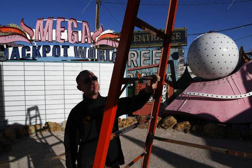 In this Jan. 23, 2018, photo, John Humphries works on an exhibit at the Neon Museum in Las Vegas. Starting this week, visitors will be able to see many of the city's classic neon signs just like they were decades ago through a type of augmented reality that projects realistic animations onto the non-working signs.