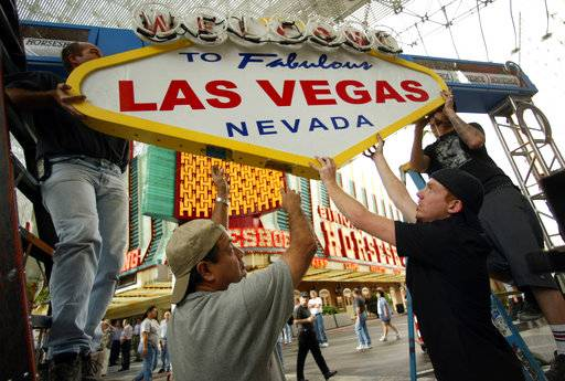 FILE - In this April 1, 2004, file photo, workers prepare the stage for a ribbon-cutting ceremony in front of Binion's Horseshoe Casino on Fremont Street in downtown Las Vegas. Forty neon signs that once drew visitors to some of Las Vegas' most iconic casino-hotels and other venues will shine again for the public starting Wednesday, Jan. 31, 2018, night at the Neon Museum.