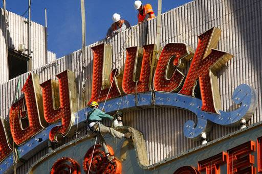 FILE - In this Oct. 27, 2011, file photo, workers prepare to remove the sign from the defunct Lady Luck Hotel and Casino in Las Vegas. Forty neon signs that once drew visitors to some of Las Vegas' most iconic casino-hotels and other venues will shine again for the public starting Wednesday, Jan. 31, 2018, night at the Neon Museum. (Jessica Ebelhar/Las Vegas Review-Journal via AP, File)