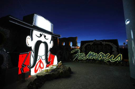 In this Jan. 24, 2018, photo, projectors light up non-working neon signs at an exhibit at the Neon Museum in Las Vegas. Starting this week, visitors will be able to see many of the city's classic neon signs just like they were decades ago through a type of augmented reality that projects realistic animations onto the non-working signs.