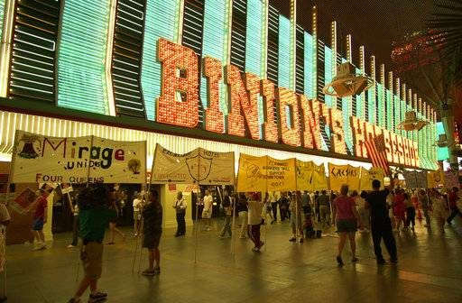 FILE - In this July 1, 2002, file photo, members of the culinary union march in downtown Las Vegas on Fremont Street at the Binion's Horseshoe. Forty neon signs that once drew visitors to some of Las Vegas' most iconic casino-hotels and other venues will shine again for the public starting Wednesday, Jan. 31, 2018, night at the Neon Museum.