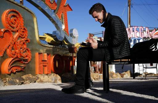 In this Jan. 23, 2018, photo, digital artist and designer Craig Winslow looks at his notebook at an exhibit at the Neon Museum in Las Vegas. Starting this week, visitors will be able to see many of the city's classic neon signs just like they were decades ago through a type of augmented reality that projects realistic animations onto the non-working signs.