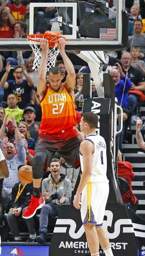 Utah Jazz center Rudy Gobert (27) dunks the ball as Golden State Warriors guard Klay Thompson (11) looks on in the first half during an NBA basketball game Tuesday, Jan. 30, 2018, in Salt Lake City.