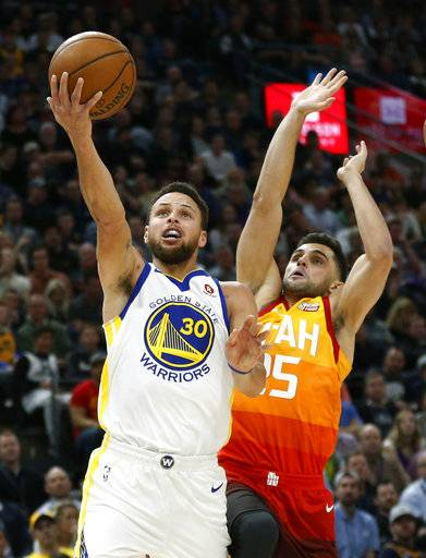 Golden State Warriors guard Stephen Curry (30) lays the ball up as Utah Jazz guard Raul Neto, right, defends in the first half during an NBA basketball game Tuesday, Jan. 30, 2018, in Salt Lake City.
