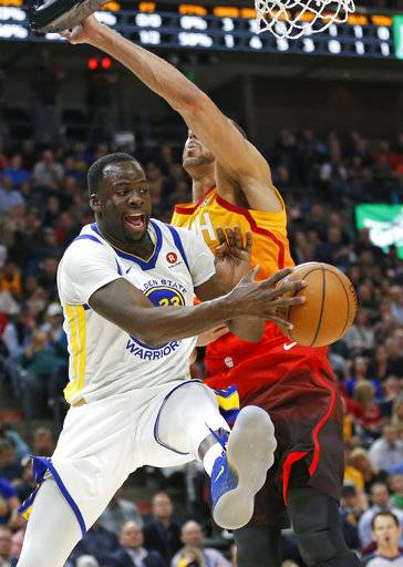 Utah Jazz center Rudy Gobert, right, defends against Golden State Warriors forward Draymond Green, left, as he passes the ball in the first half during an NBA basketball game Tuesday, Jan. 30, 2018, in Salt Lake City.