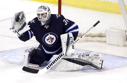 Winnipeg Jets' goaltender Michael Hutchinson (34) makes a glove save against the Tampa Bay Lightning during the third period of an NHL hockey game, Tuesday, Jan. 30, 2018 in Winnipeg, Manitoba. (Trevor Hagan/The Canadian Press via AP)