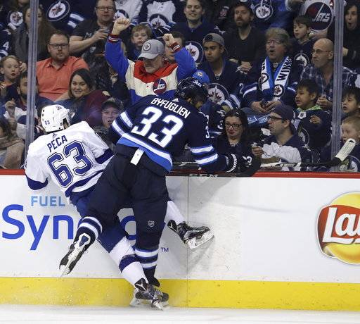 Winnipeg Jets' Dustin Byfuglien (33) delivers a big hit on Tampa Bay Lightning's Matthew Peca (63) during the second period of an NHL hockey game, Tuesday, Jan. 30, 2018 in Winnipeg, Manitoba. (Trevor Hagan/The Canadian Press via AP)