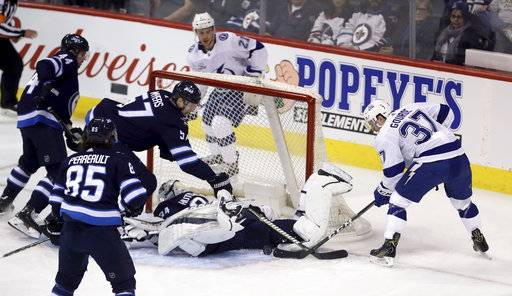 Winnipeg Jets' goaltender Michael Hutchinson (34) makes a save on Tampa Bay Lightning's Yanni Gourde (37) during the first period of an NHL hockey game, Tuesday, Jan. 30, 2018 in Winnipeg, Manitoba. (Trevor Hagan/The Canadian Press via AP)
