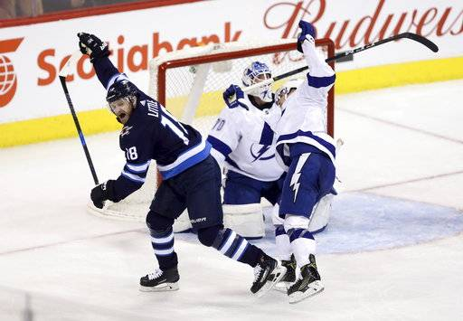 Winnipeg Jets' Bryan Little (18) celebrates after scoring on Tampa Bay Lightning's goaltender Louis Domingue (70) with Yanni Gourde (37) trying to check him during the third period of an NHL hockey game, Tuesday, Jan. 30, 2018 in Winnipeg, Manitoba. (Trevor Hagan/The Canadian Press via AP)