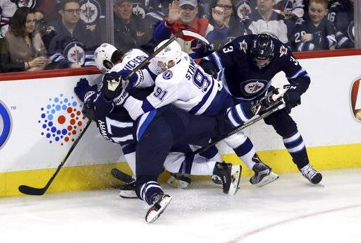 Tampa Bay Lightning's Steven Stamkos (91) hits Winnipeg Jets' Adam Lowry (17) with Nikita Kucherov (86) and Tucker Poolman (3) battling along the boards during the third period of an NHL hockey game, Tuesday, Jan. 30, 2018 in Winnipeg, Manitoba. (Trevor Hagan/The Canadian Press via AP)