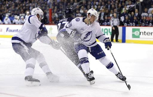 Winnipeg Jets' Nikolaj Ehlers (27) evades Tampa Bay Lightning's Victor Hedman (77) and Jake Dotchin (59) during the second period of an NHL hockey game, Tuesday, Jan. 30, 2018 in Winnipeg, Manitoba. (Trevor Hagan/The Canadian Press via AP)