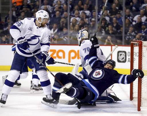 Winnipeg Jets' Matt Hendricks (15) is tripped up by Tampa Bay Lightning's Braydon Coburn (55) behind goaltender Louis Domingue (70) during the second period of an NHL hockey game, Tuesday, Jan. 30, 2018 in Winnipeg, Manitoba. (Trevor Hagan/The Canadian Press via AP)