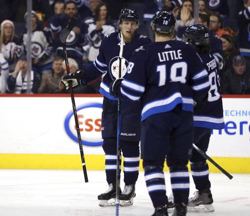 Winnipeg Jets' Patrik Laine (29) celebrates with Bryan Little (18) and Mathieu Perreault (85) after scoring against the Tampa Bay Lightning during the second period of an NHL hockey game, Tuesday, Jan. 30, 2018 in Winnipeg, Manitoba. (Trevor Hagan/The Canadian Press via AP)