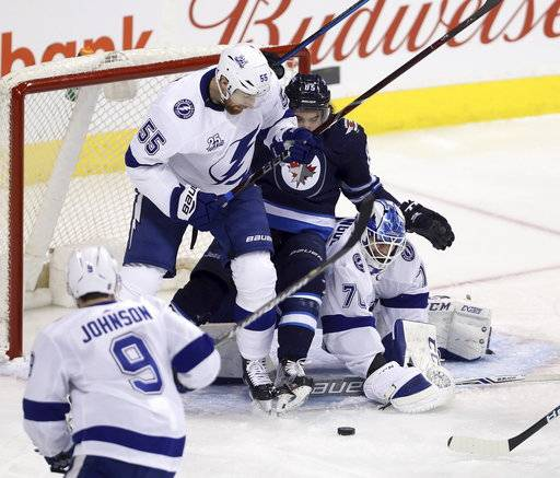 Tampa Bay Lightning's Braydon Coburn (55) bumps Winnipeg Jets' Mathieu Perreault (85) into goaltender Louis Doningue (70) during the first period of an NHL hockey game, Tuesday, Jan. 30, 2018 in Winnipeg, Manitoba. (Trevor Hagan/The Canadian Press via AP)