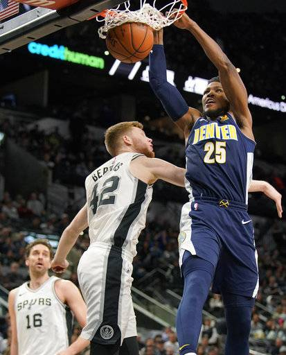 Denver Nuggets' Malik Beasley (25) dunks over San Antonio Spurs' Davis Bertans during the first half of an NBA basketball game Tuesday, Jan. 30, 2018, in San Antonio.