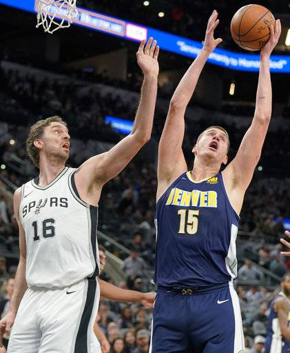 Denver Nuggets' Nikola Jokic (15) and San Antonio Spurs' Pau Gasol reach for a rebound during the first half of an NBA basketball game Tuesday, Jan. 30, 2018, in San Antonio.
