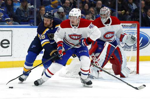 Montreal Canadiens' Byron Froese (42) and St. Louis Blues' Kyle Brodziak (28) chase the puck as Canadiens goalie Carey Price, right, watches during the second period of an NHL hockey game Tuesday, Jan. 30, 2018, in St. Louis.